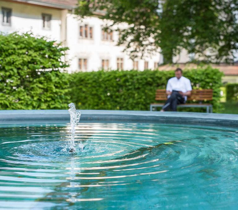 Entspannung im Garten des Kloster Fischingen. Man liest Buch bei Brunnen