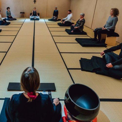 Menschen bei meditativem Yoga in Meditationsraum