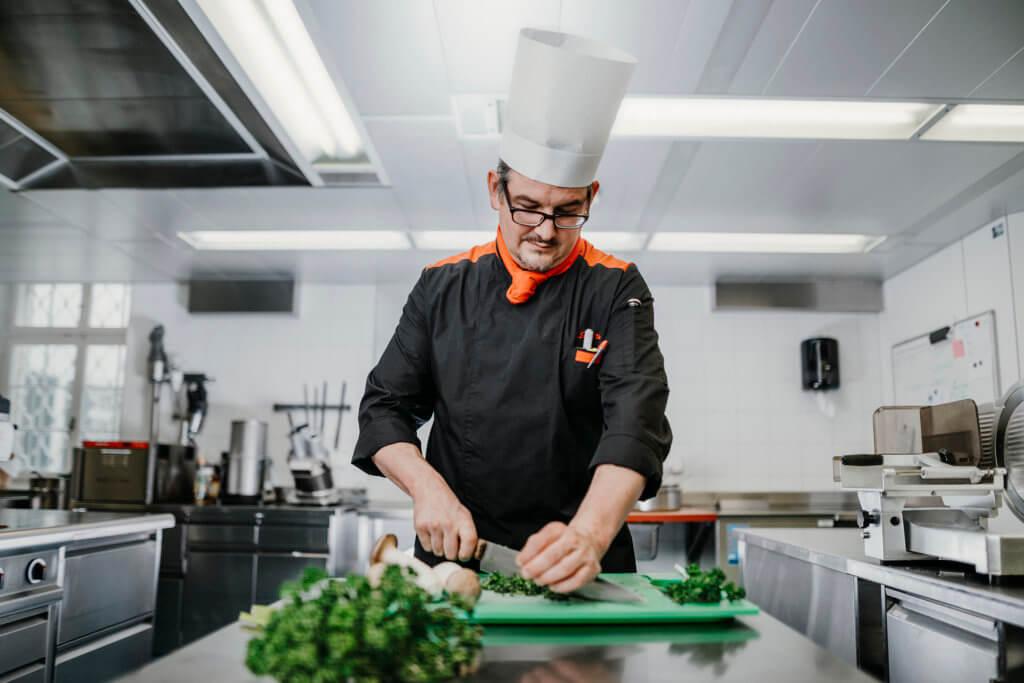 Koch in Klosterküche beim Schneiden von Gemüse